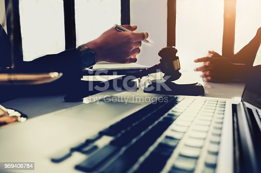 istock law and justice concept, client discussion lawyer judgement lawsuit with holding pen, law book,gavel and scales of justice at table in office. 959406784