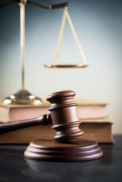 Concepto de derecho y la justicia. Mazo de juez, libros, balanza de la justicia. Fondo de piedra gris, reflexiones sobre el piso, lugar para tipografía. Tema de la sala de audiencias. - foto de stock