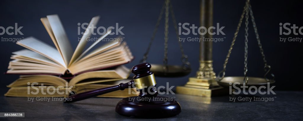 Law and Justice concept. Mallet of the judge, books, scales of justice. Gray stone background, reflections on the floor, place for typography. Courtroom theme. stock photo