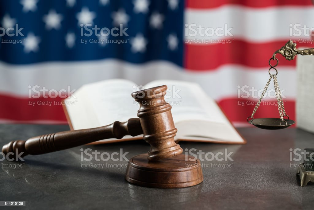Law and justice symbols on USA flag background. stock photo