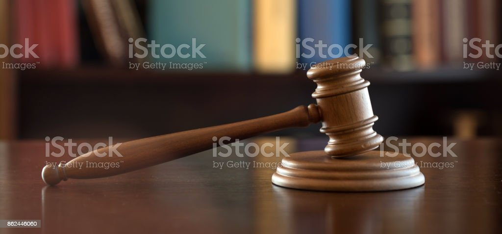 Law and Justice theme. Gavel of the Judge, books, scales of justice. Brown background, stock photo