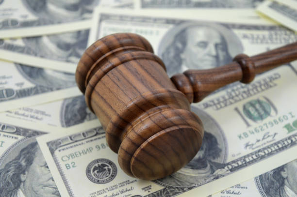 Law and Money An image focused on the legal side of monetary gains using a gavel and an abundance of American cash as a background. lawsuit stock pictures, royalty-free photos & images