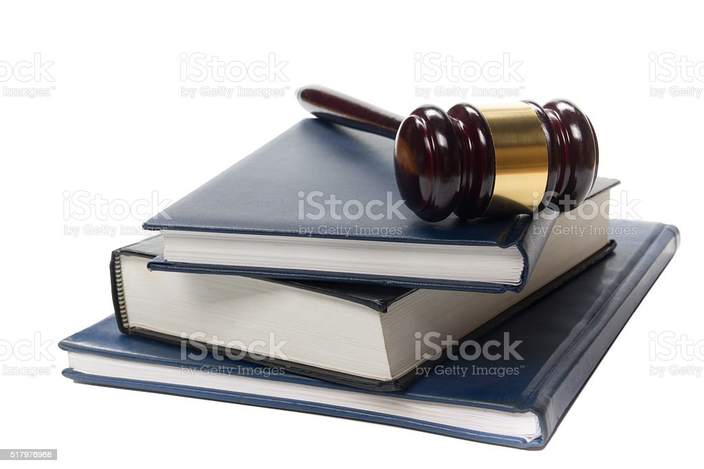 Law book with a wooden judges gavel on table in stock photo