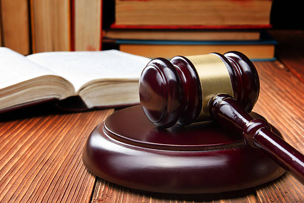 Law book with wooden judges gavel on table in a Law concept - Law book with a wooden judges gavel on table in a courtroom or law enforcement office jurist stock pictures, royalty-free photos & images