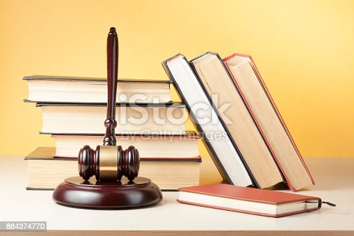 istock Law concept. Book with wooden judges gavel on table in a courtroom or enforcement office. 884374770