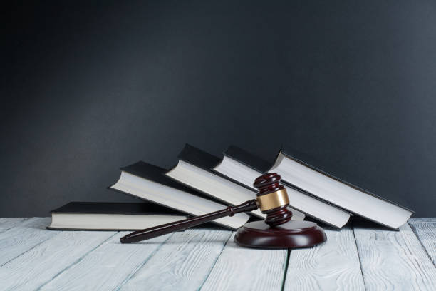 Law concept - Open law book with a wooden judges gavel on table in a courtroom or law enforcement office isolated on white background. Copy space for text stock photo