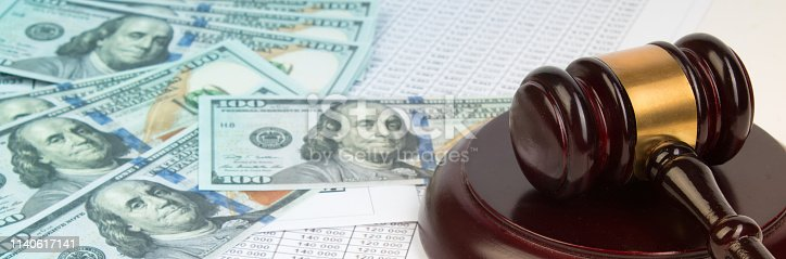 Law concept or auction concept. Dollar bills , judge's gavel on white background. closeup of a gavel on cash, from above