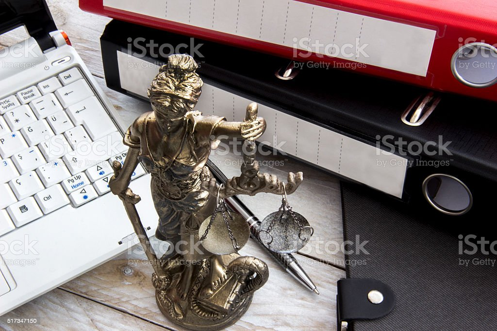 Law concept, statue, laptop and folder on wood table stock photo