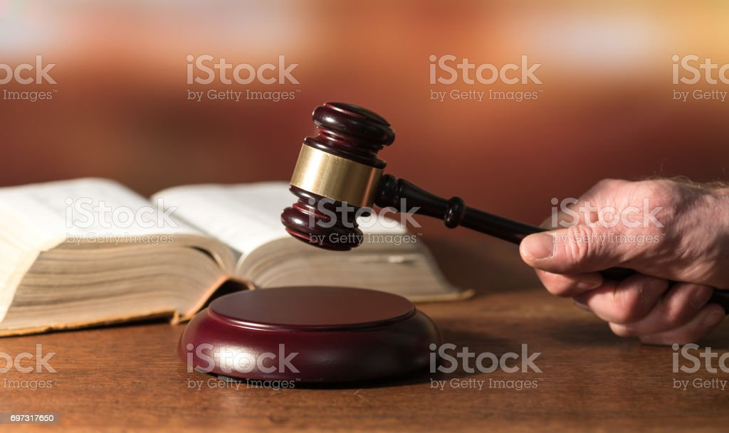 Law concept with hand holding a judge gavel stock photo