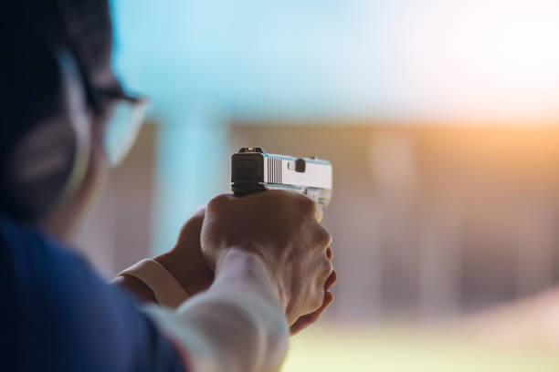 law enforcement aim pistol by two hand in academy shooting range law enforcement aim pistol by two hand in academy shooting range in flare and vintage color advanced tactical fighter stock pictures, royalty-free photos & images