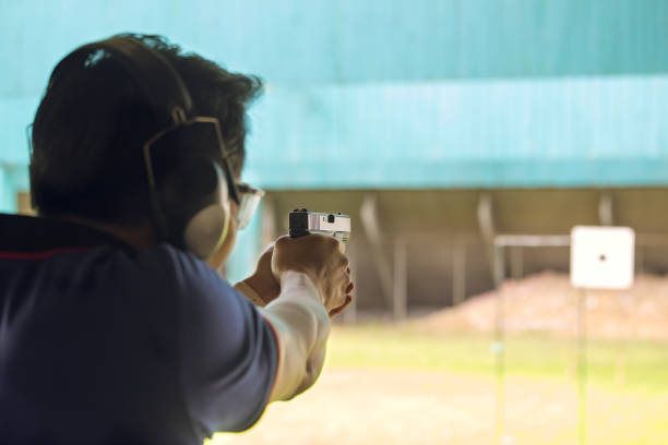law enforcement aim pistol by two hand in academy shooting range law enforcement aim pistol by two hand in academy shooting range focus on pistol in vintage color advanced tactical fighter stock pictures, royalty-free photos & images