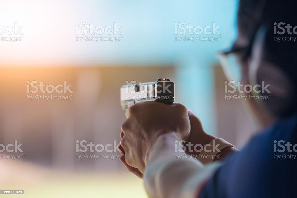 aplicação da lei apontar a pistola por duas mão na Academia, tiro ao alvo - foto de acervo