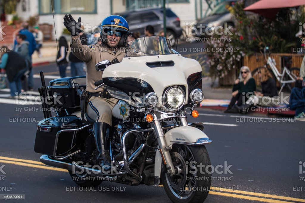 Law enforcement officer interacting with crowd by smiling. stock photo