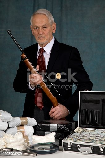 Police Officer with packages of illicit substance on table, holding rifle looking at camera with a defiant look as if to say we got you!