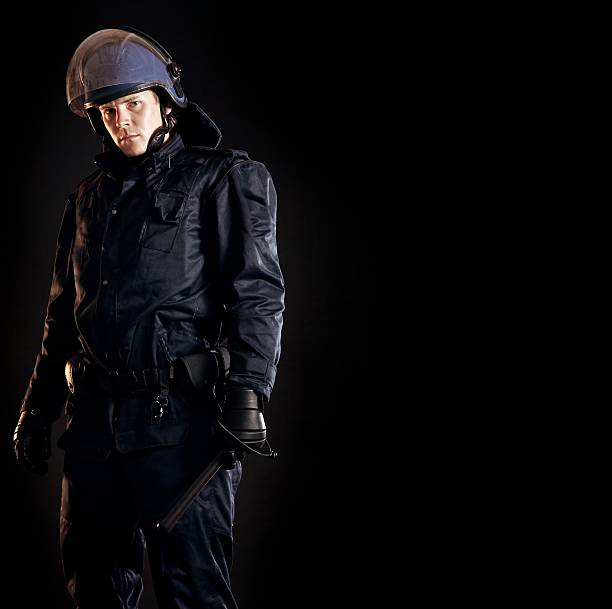 Law Enforcer Ready for Crowd Control Law enforcer in protective uniform ready for crowd control isolated on black riot police stock pictures, royalty-free photos & images