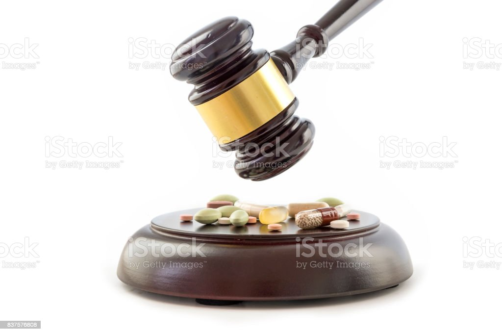 Law gavel and drugs, tablets and pills on the wooden sound block, isolated on a white background, justice and medicine concept stock photo