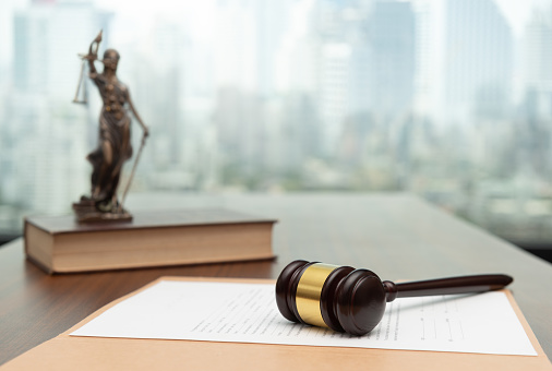 Judges gavel on legal document with statue of justice on law books.  concept of legal ruling Jurisprudence, law education.