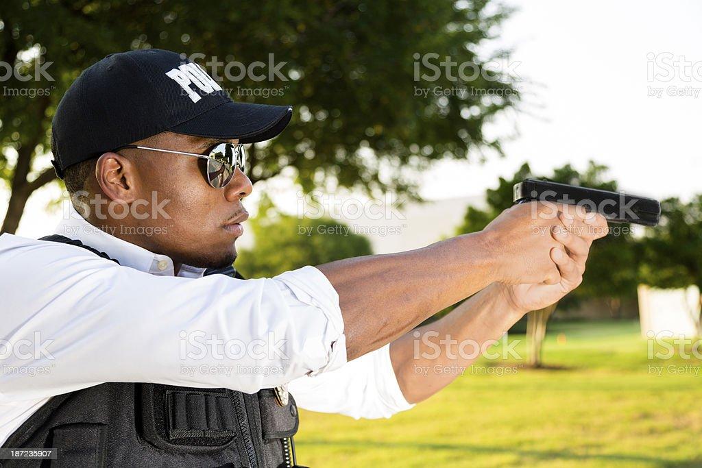 Law:  Local policeman aims his gun at criminal. royalty-free stock photo