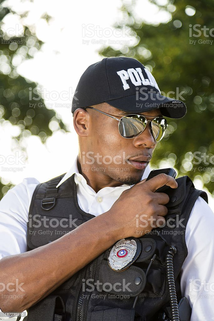 Law:  Local policeman calls in a crime on his radio. royalty-free stock photo