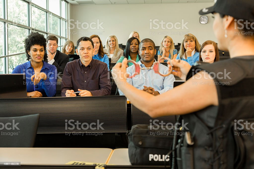 Law:  Policewoman speaks to police cadets in classroom. Handcuffs. stock photo