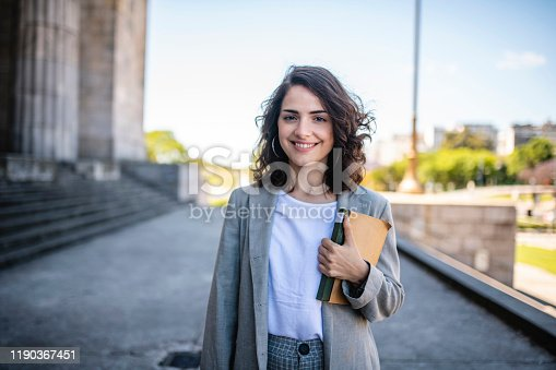 Close-up of relaxed female law student in casual attire standing with book at entrance to university in Buenos Aires.