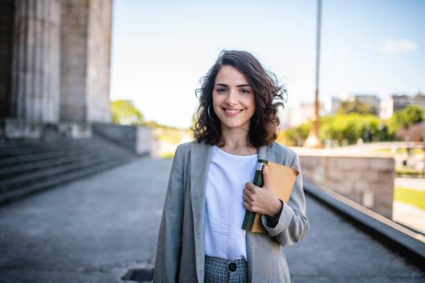 站在大學大樓入口處的法律系學生 - 年輕女性 個照片及圖片檔