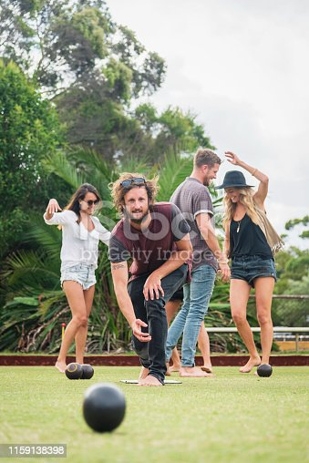 Australian fashionable group of friends playing lawn bowls outdoors together. Young man just rolled the bowl looking concentrated for his result. Sydney, Australia.