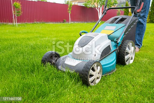 A lawn mover is cutting green grass, the gardener is working with a lawn mower, a close-up, the yard of a private house.