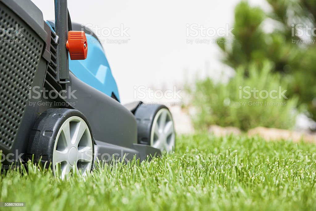 Lawn mower on a green meadow stock photo