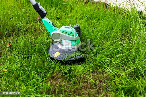 Lawn mower cutting green grass in residential area.