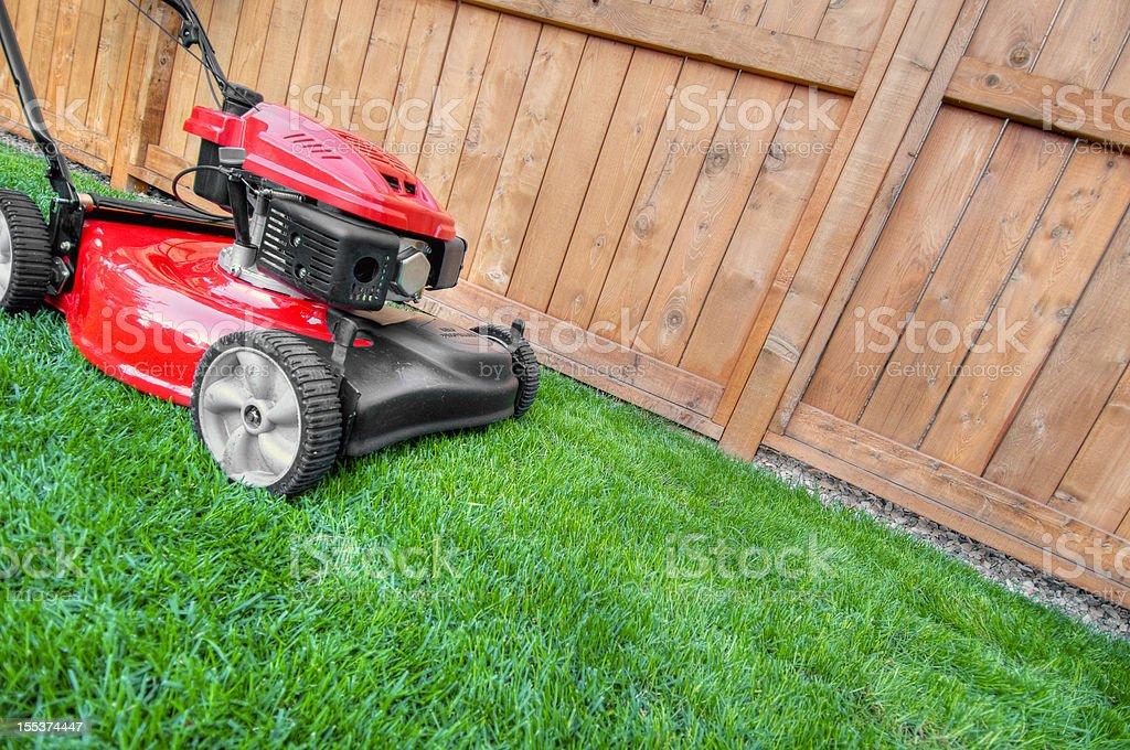 Lawn mower on lush grass in backyard royalty-free stock photo