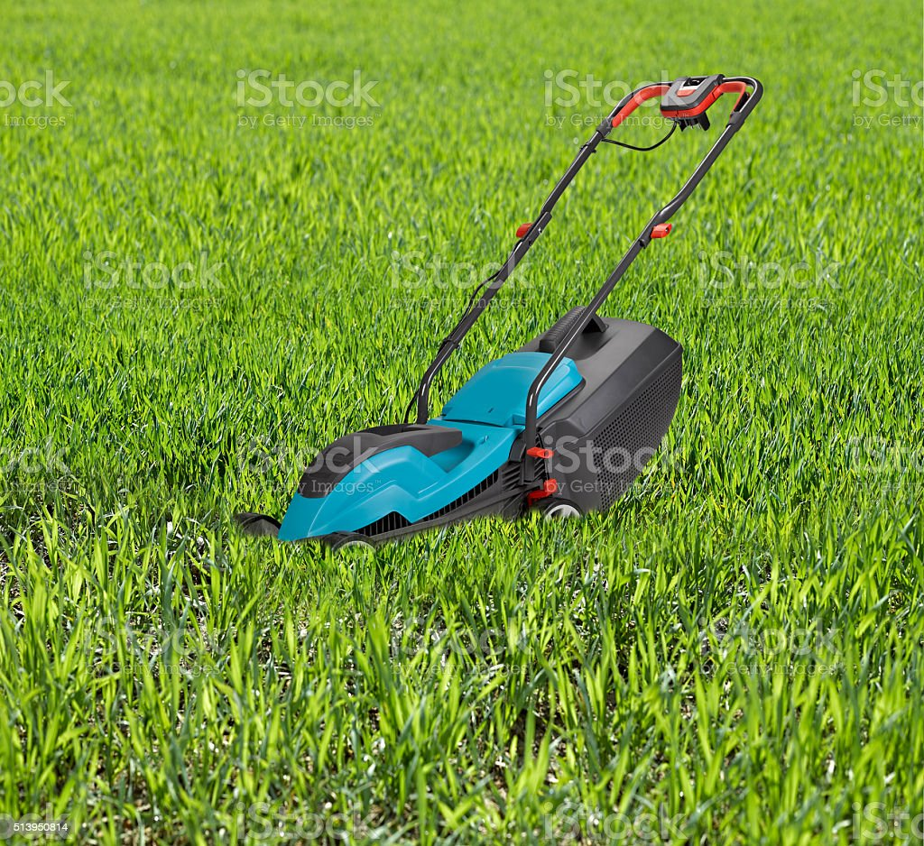 Lawn mower surrounded by high grass. stock photo