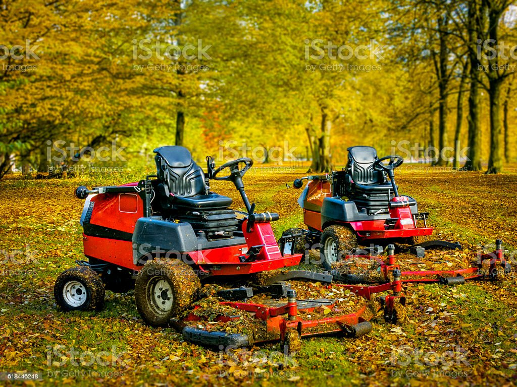 Lawn mowers in autumn park,two of them stock photo