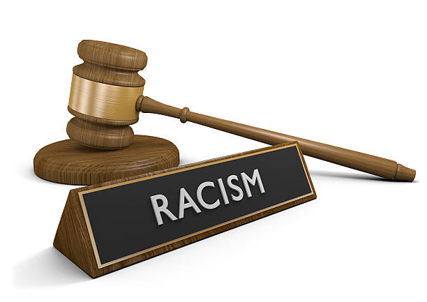 Laws and legislation against racism and discriminatory acts, 3D rendering Wooden court gavel next to a sign that says racism, rendered in 3D over a white background. discriminatory stock pictures, royalty-free photos & images