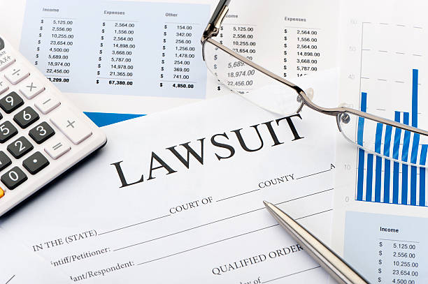 Lawsuit form an a desk Lawsuit form an a desk with pen and calculator lawsuit stock pictures, royalty-free photos & images