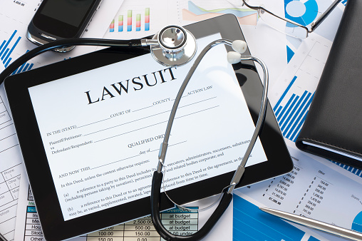 Lawsuit form with a stethoscope on a desk