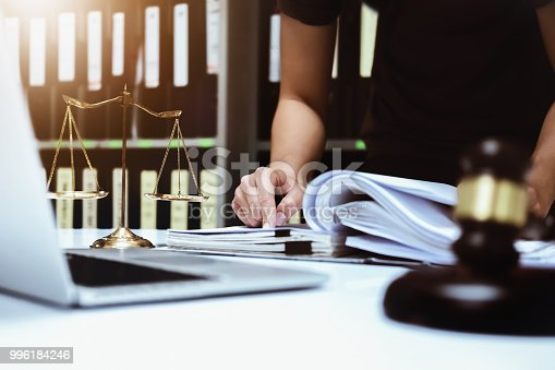 istock Lawsuits and Laws concept, Male lawyer working with contract papers with using using computer laptop, wooden gavel and justice scales in courtroom. 996184246