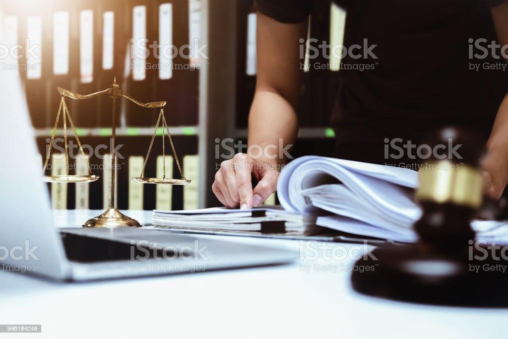 Klagen und Gesetze Konzept, Papiere männlichen Anwalt arbeitet mit Vertrag bei der Verwendung mit Computer Laptop, hölzernen Hammer und Gerechtigkeit Skalen im Gerichtssaal. – Foto