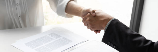 Lawyer and client handshake with contract agreement signing in law firm. stock photo