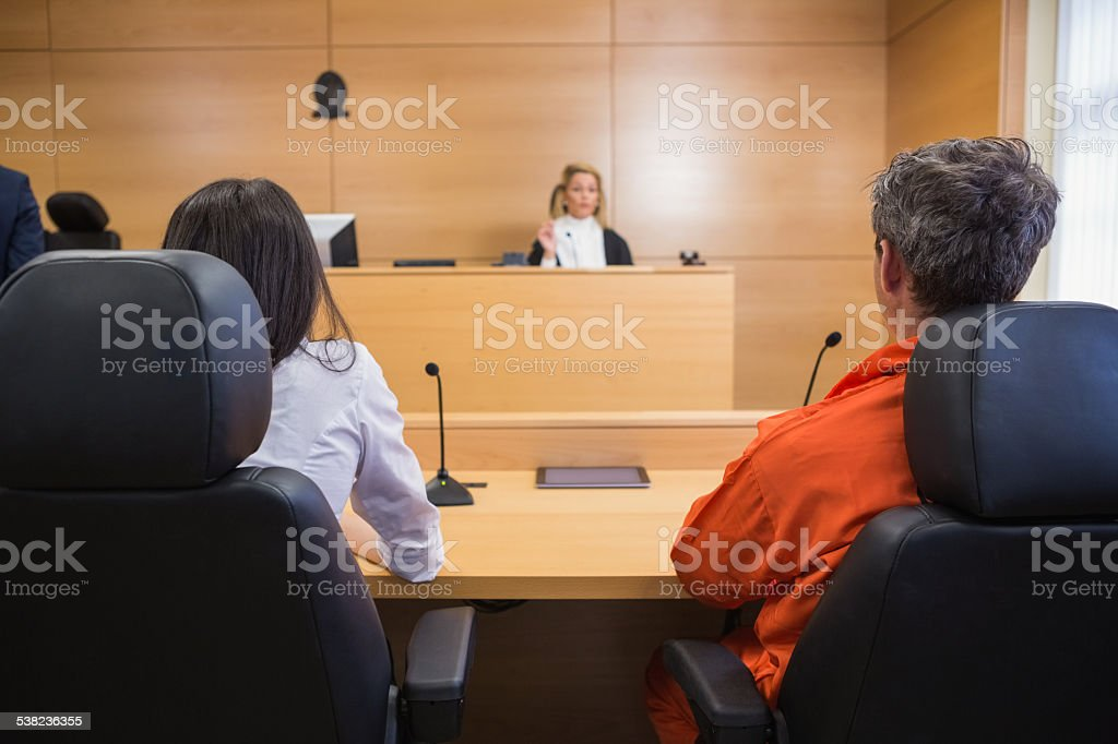 Lawyer and client listening to judge stock photo