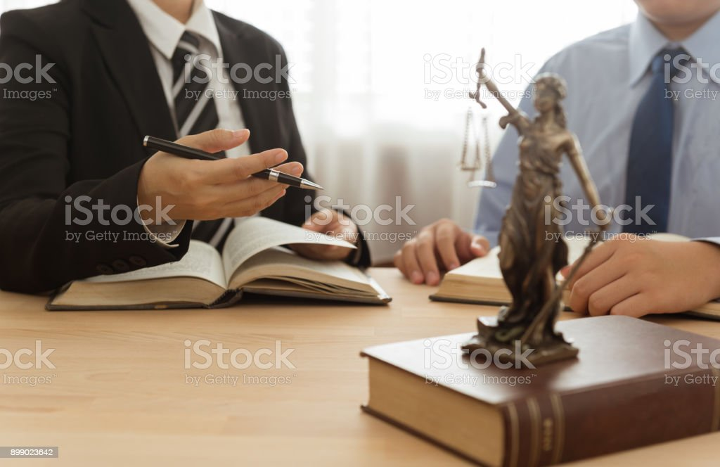 lawyer and client Law, Legal advice, Legislation concept. Lady justice on law book with lawyer and client in law office. Adult Stock Photo