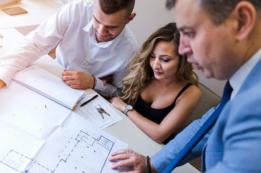 938640610 istock photo Lawyer and his clients revising blueprints 1180087258