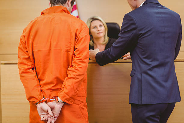 Lawyer and judge speaking next to the criminal in handcuffs Lawyer and judge speaking next to the criminal in handcuffs in the court room criminal stock pictures, royalty-free photos & images