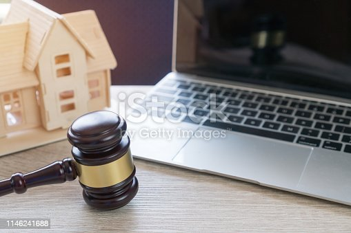 istock Lawyer business real estate property agent, home loan or divorce. Concept of Conflict lawsuit from not paying home debt, therefore requiring judgment prosecution. Judge hammer with house on Computer 1146241688