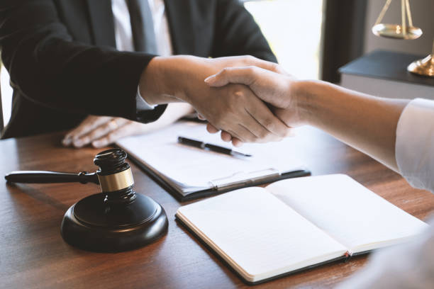 Lawyer consult hands shaking with client in courtroom. stock photo