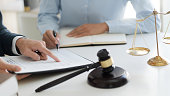 istock Lawyer consultant explaining to client with law suit. 1268237343