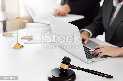 istock lawyer consultant give an advice with client at law firm. 1127489701