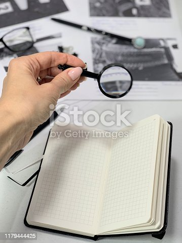 istock Lawyer desk, magnifier in hand. 1179444425