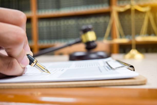 rechtsanwalt detail eines richters sitzt an seinem schreibtisch, neue gesetze und rechtsvorschriften und notizen zu studieren. selektiven fokus - rechtsassistent stock-fotos und bilder