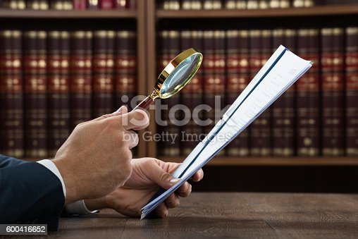 istock Lawyer Examining Documents With Magnifying Glass 600416652